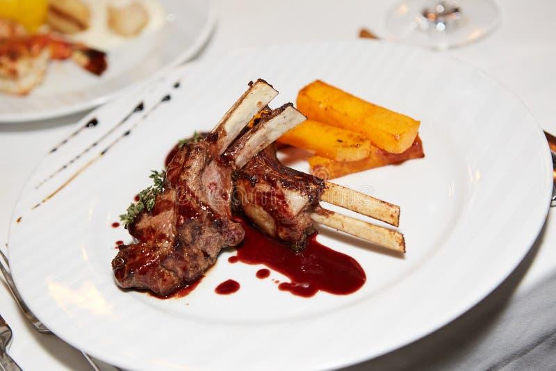 Schließen Sie herauf geschmackvolle gegrillte Schweinefleisch-Rippe und Fried Potatoes auf weißer Platte lizenzfreie stockfotos