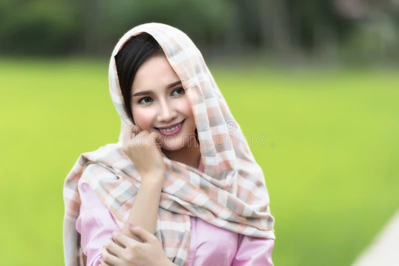 Schließen Sie herauf Gesicht der schönen Laofrau, die lokale Tradition auf grünem Reisfeld trägt lizenzfreie stockfotos
