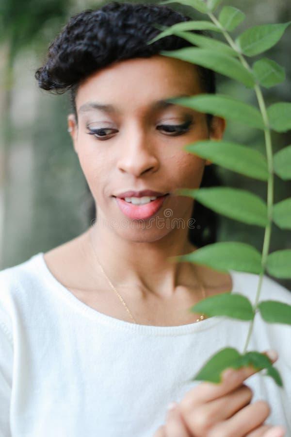 Schließen Sie herauf Gesicht der schwarzen weiblichen Person, die grünes Blatt hält und Bluse der Knalle und des Tragens haben we stockbild