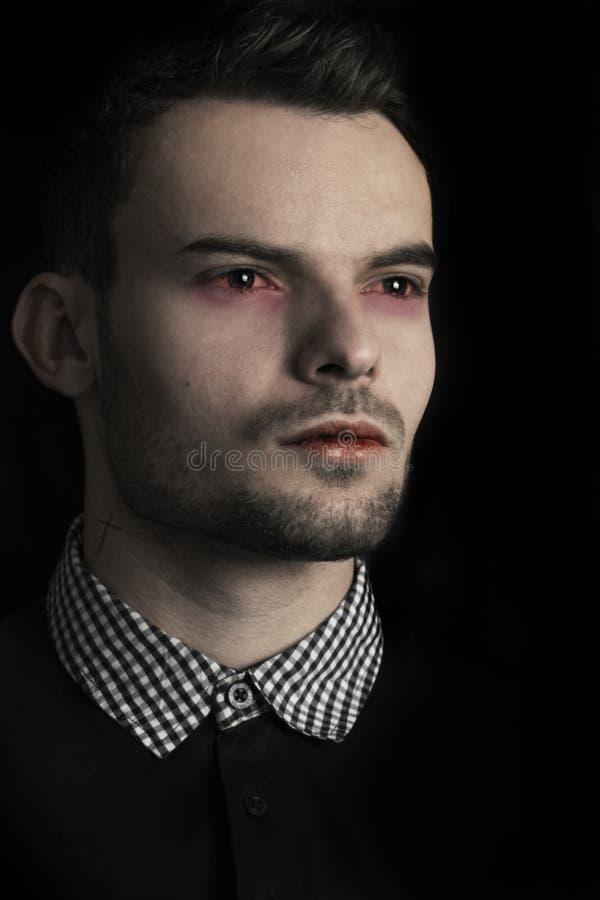 Schließen Sie herauf Gesicht eines hübschen Vampirs-Mannes Männliches Modell der Mode als Vampir mit Tätowierungskreuz auf dem Ha lizenzfreie stockbilder