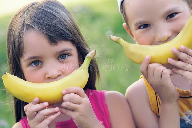 Schließen Sie herauf Gesichter eines schönen jungen kaukasischen Mädchens und des Jungen mit Bananenlächeln auf Naturhintergrund lizenzfreies stockbild