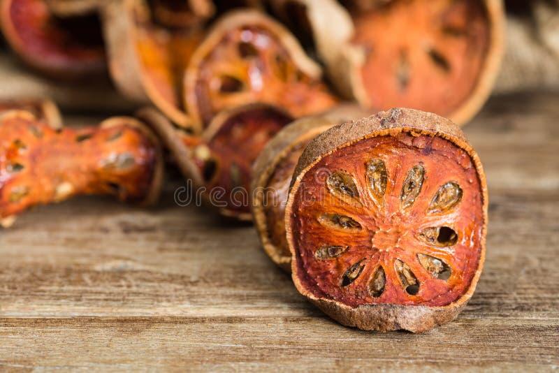 Schließen Sie herauf getrocknete Scheibe bael Frucht auf Holztisch stockfotografie