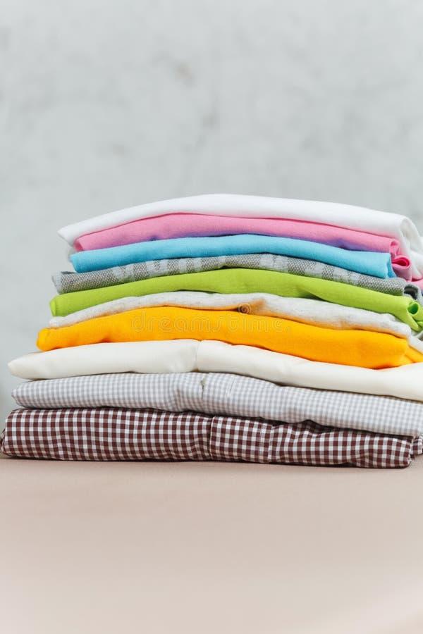 Schließen Sie herauf gewaschene Wäscherei des Dampfbügeleisens bunte Kleidung auf weißem Hintergrund haushaltung Kopieren Sie Rau lizenzfreie stockbilder