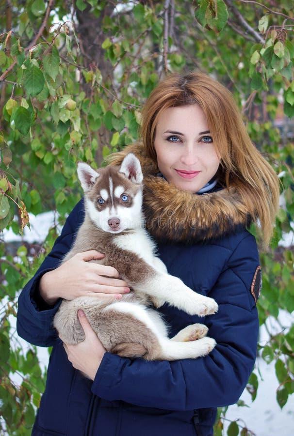 Schließen Sie herauf glücklichen Fraueneigentümer und heiseren Hund am Wintertag stockfotos
