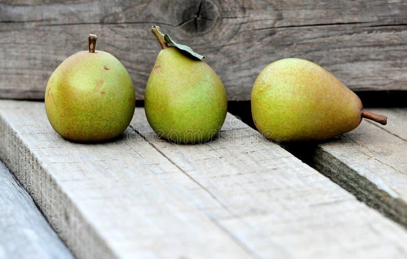 Schließen Sie herauf grüne Birnen auf der hölzernen Planke mit hölzernem Hintergrund lizenzfreie stockbilder