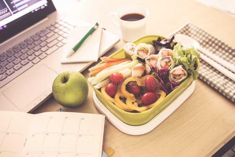 Schließen Sie herauf grüne Brotdose auf dem Arbeitsarbeitsplatz Schreibtisch, heilen Sie stockfoto