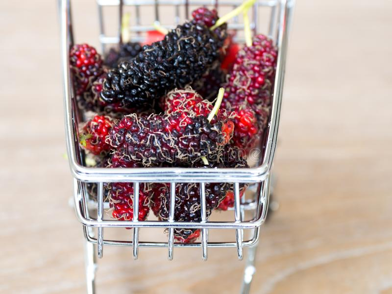 Schließen Sie herauf Gruppe Maulbeeren im roten Warenkorb auf Holztisch Maulbeere dieses eine Frucht und kann herein gegessen wer stockfotos