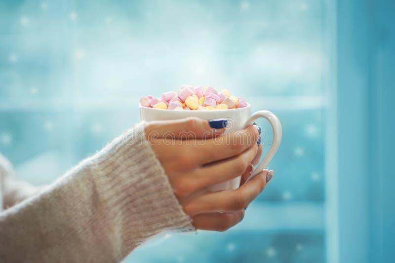 Schließen Sie herauf Hände der Frau der jungen Frau mit der Maniküre, die eine Schale heißen Kakao mit nahem Fensterinnenschnee d lizenzfreies stockfoto