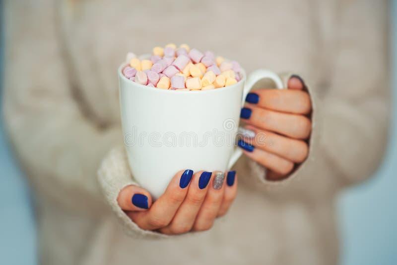 Schließen Sie herauf Hände der Frau der jungen Frau mit der Maniküre, die eine Schale heißen Kakao mit nahem Innenfenster des Eib stockfoto