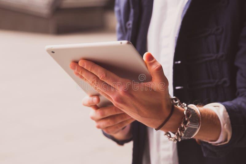 Schließen Sie herauf Hände des jungen Mannes, der Tablette auf Straße verwendet stockfoto