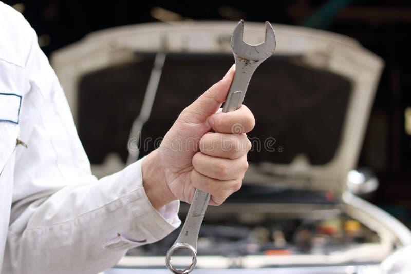 Schließen Sie herauf Hände des professionellen jungen Mechanikermannes, der Schlüssel mit Auto in der offenen Haube am Garagenhin lizenzfreie stockfotos