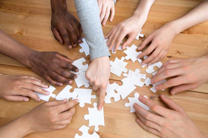 Schließen Sie herauf Hände des zusammenbauenden Puzzlespiels der verschiedenen Leute lizenzfreie stockfotos