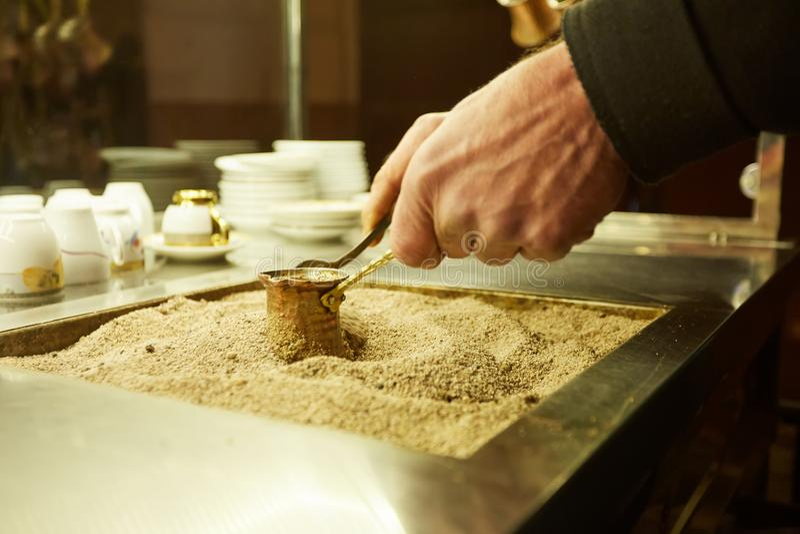 Schließen Sie herauf Hände eines Mannes, der türkischen Kaffee auf heißem goldenem Sand kocht lizenzfreies stockfoto