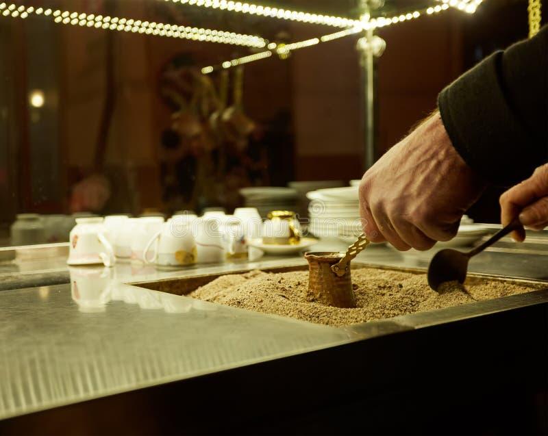 Schließen Sie herauf Hände eines Mannes, der türkischen Kaffee auf heißem goldenem Sand kocht lizenzfreie stockfotografie
