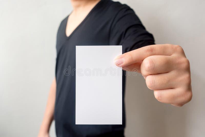 Schließen Sie herauf Hand des zufälligen Mannschwarzhemdes, das an Visitenkarte hält lizenzfreies stockfoto