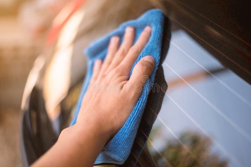 Schließen Sie herauf Handgriff Auto-Abwischen auf Auto-Spiegel lizenzfreie stockfotos