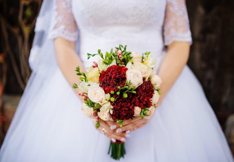 Schließen Sie herauf Hochzeitsblumenstrauß mit den roten und weißen Blumen an den Händen von lizenzfreie stockfotografie