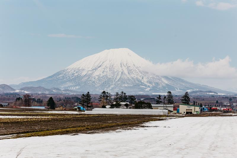 Schließen Sie herauf inaktiv stratovolcano Berg Yotei mit Dorf und Schneedecke aus den Grund im Winter in Hokkaido, Japan stockfotos