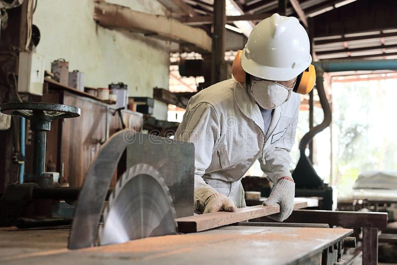 Schließen Sie herauf junge hölzerne Arbeitskraft in der Uniform und in Schutzausrüstung, die ein Stück Holz auf Tabellensägemasch stockfotografie