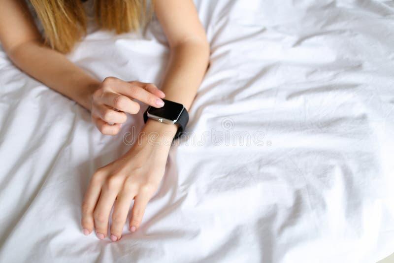 Schließen Sie herauf kaukasische weibliche Hände mit intelligenter Uhr im weißen Leinenhintergrund lizenzfreies stockfoto