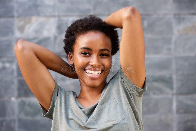 Schließen Sie herauf lächelnde junge schwarze Frau mit den Händen hinter Kopf stockbilder
