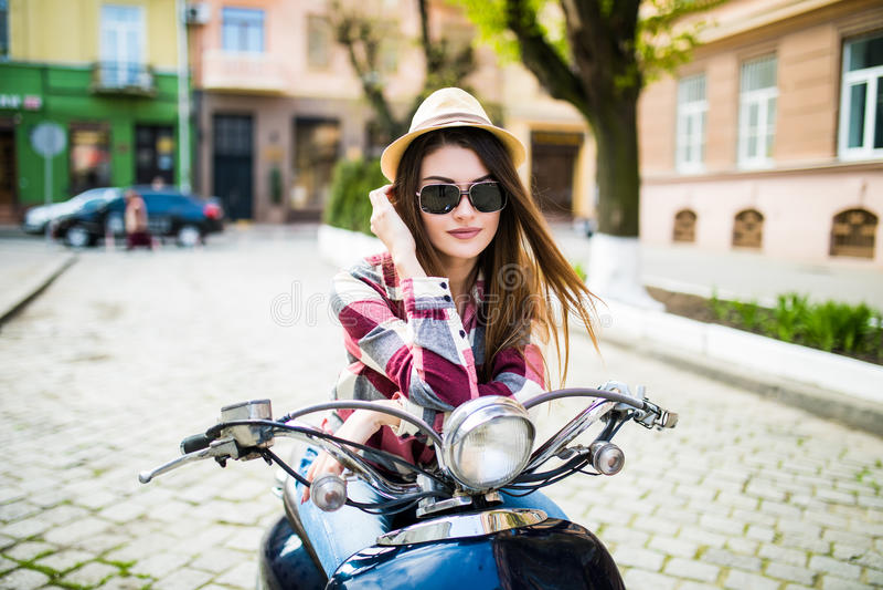 Schließen Sie herauf Lebensstilbild der jungen modernen Frau in der zufälligen Ausstattung, die auf Roller auf der Straße sitzt T lizenzfreies stockfoto