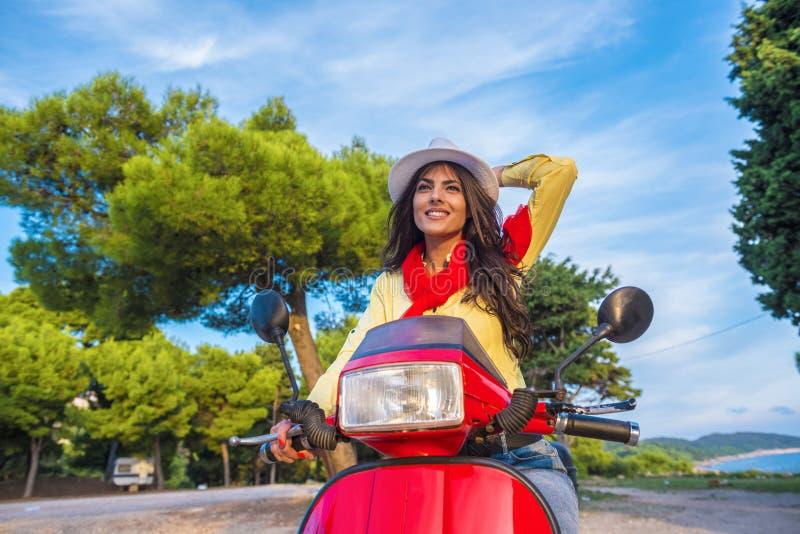 Schließen Sie herauf Lebensstilbild der jungen modernen Frau in der zufälligen Ausstattung, die auf Roller auf der Straße sitzt stockfotografie