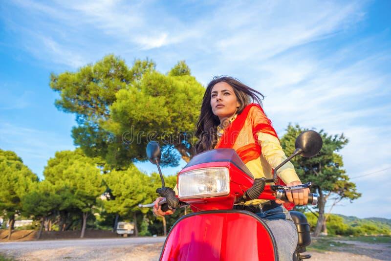 Schließen Sie herauf Lebensstilbild der jungen modernen Frau in der zufälligen Ausstattung, die auf Roller auf der Straße sitzt lizenzfreie stockbilder