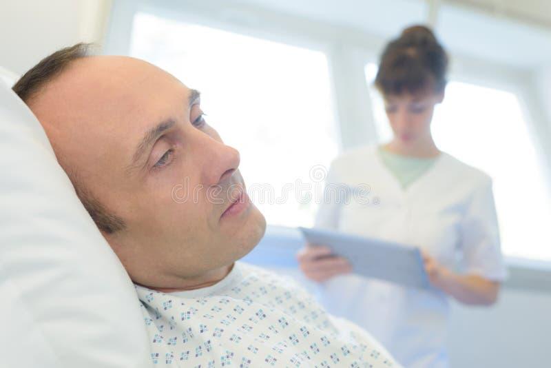 Schließen Sie herauf männlichen Patienten mit Krankenschwester stockfotografie