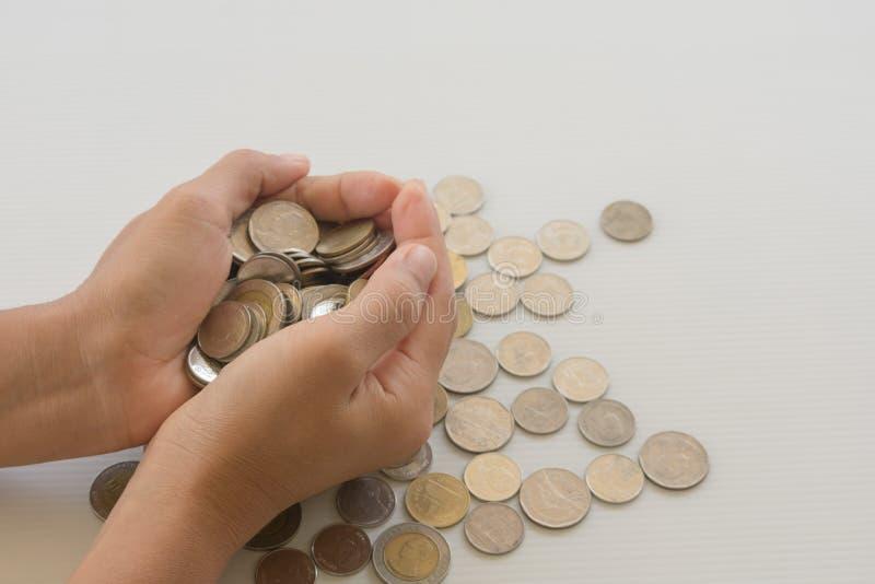Schließen Sie herauf Münzen in den Händen auf weißem Tabellenhintergrund Stecken eines Geldes in eine piggy Querneigung lizenzfreie stockfotografie