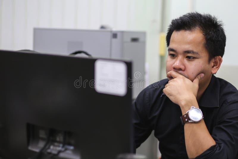 Schließen Sie herauf Mann im Büro, das schwer arbeitet stockfotografie