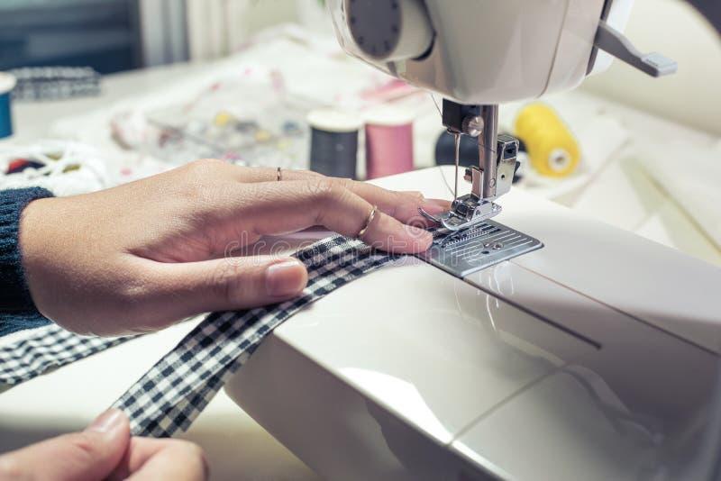 Schließen Sie herauf Modedesignerschneider, den Kleidung mit Ausrüstung näht stockbild