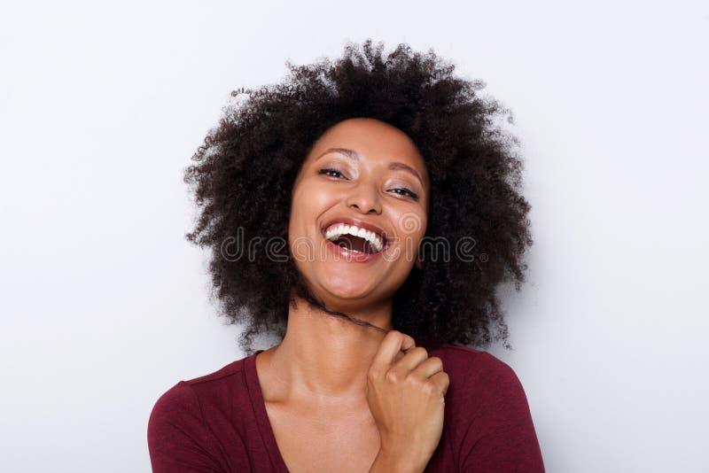 Schließen Sie herauf nette junge afrikanische Frau mit der Hand im Haar und im Lachen lizenzfreie stockbilder