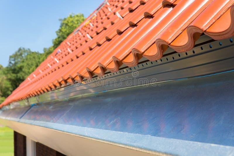 Schließen Sie herauf neue Gosse mit Dachplatten lizenzfreie stockfotos