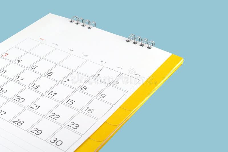 Schließen Sie herauf Papptischkalender mit den Tagen und Datum, die auf blauem Hintergrund lokalisiert werden lizenzfreies stockbild