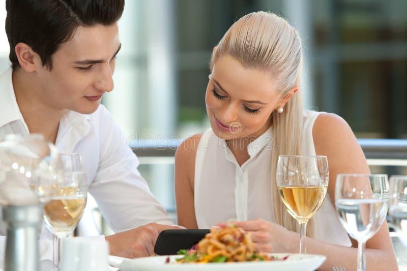 Nette Paare, die intelligentes Telefon auf Abendessen betrachten. lizenzfreies stockfoto