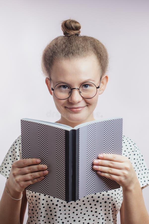 Schließen Sie herauf Porträt der lächelnden jungen Frau, die ein Buch hält stockfotos