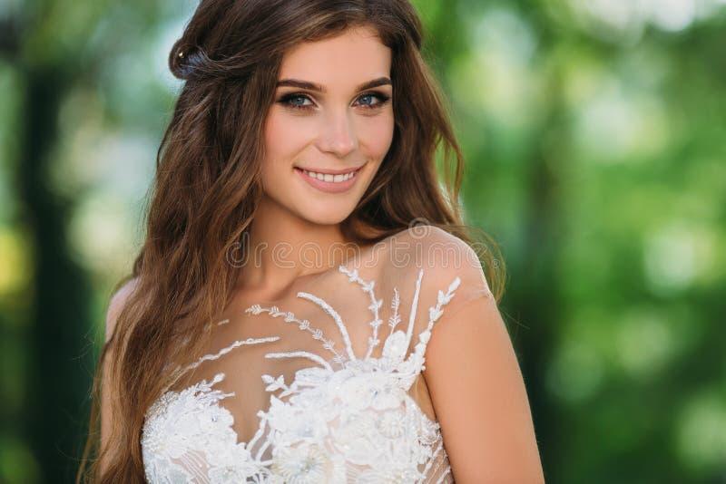 Schließen Sie herauf Porträt der netten jungen Braut mit den langen Haaren, die im schönen weißen Heiratkleid gekleidet werden Hü lizenzfreie stockfotografie