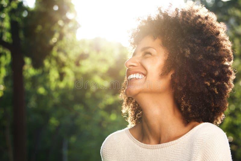Schließen Sie herauf Porträt der schönen überzeugten Frau, die in der Natur lacht stockfotografie