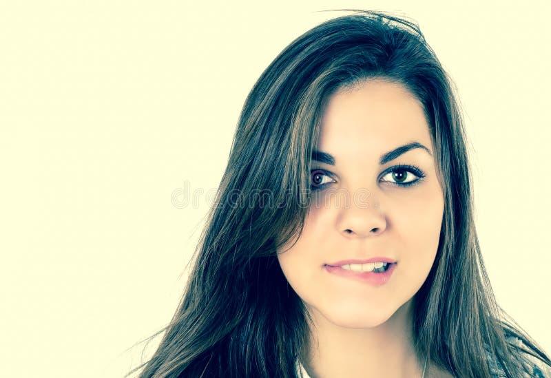Schließen Sie herauf Porträt der schönen Brunettes, das ihre Lippe auf Gelb getrenntem Hintergrund beißt stockfotografie