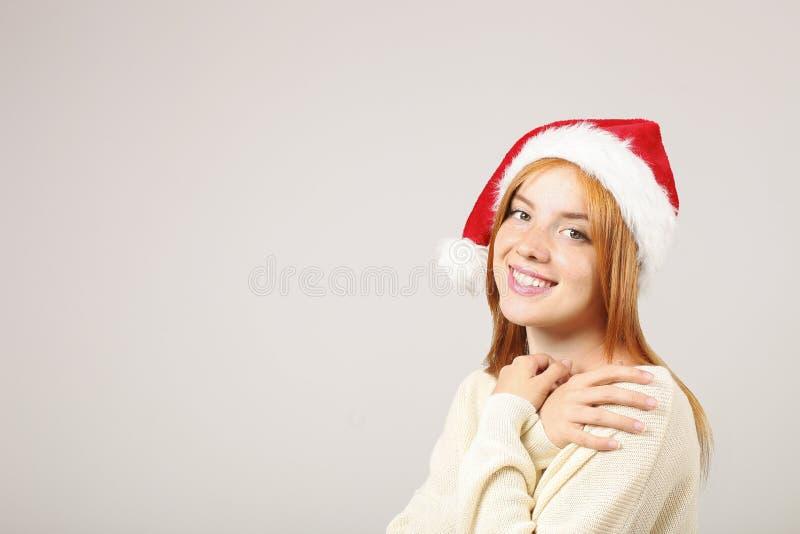Schließen Sie herauf Porträt der schönen redheaded jungen Frau, die Santa Claus-Hut u. weiße Strickjacke mit erfülltem Gesichtsau lizenzfreie stockbilder