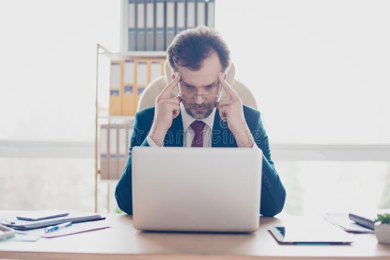Schließen Sie herauf Porträt des ernsten fokussierten Geschäftsmannes, der an sitzt stockfotografie