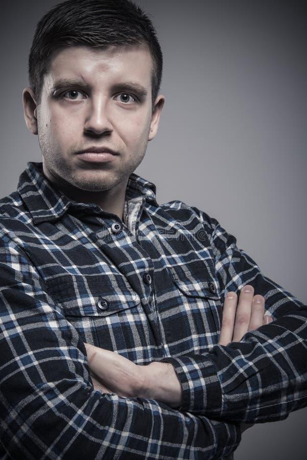 Schließen Sie herauf Porträt des Junge verfassten (sentence Mannes, der überprüftes Hemd mit den gekreuzten Armen trägt stockbilder