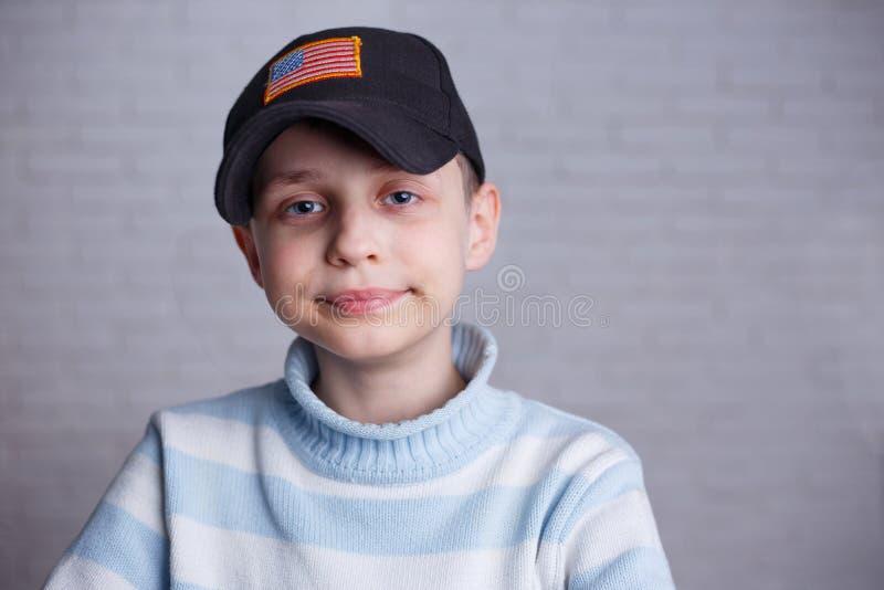 Schließen Sie herauf Porträt des netten Jungen in der Baseballmütze mit USA-Flagge stri stockfoto