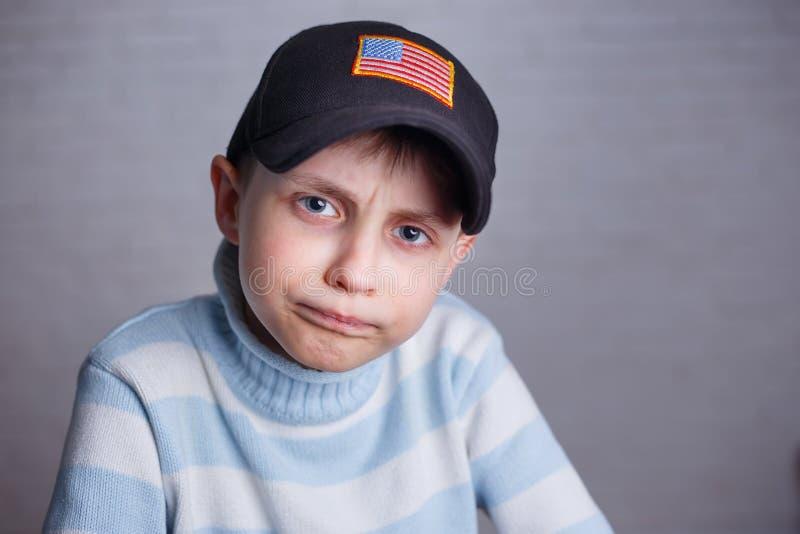 Schließen Sie herauf Porträt des netten Jungen in der Baseballmütze mit USA-Flagge stri stockfotografie