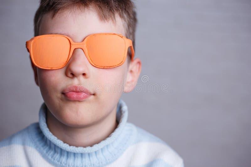 Schließen Sie herauf Porträt des netten Jungen in der orange Sonnenbrille mit undurchsichtigem L lizenzfreies stockbild