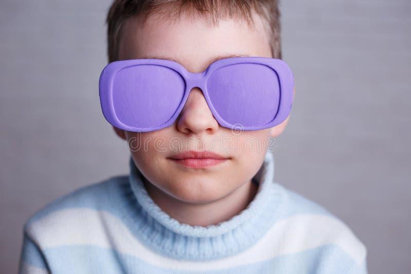 Schließen Sie herauf Porträt des netten Jungen in der violetten Sonnenbrille mit undurchsichtigem L lizenzfreie stockbilder