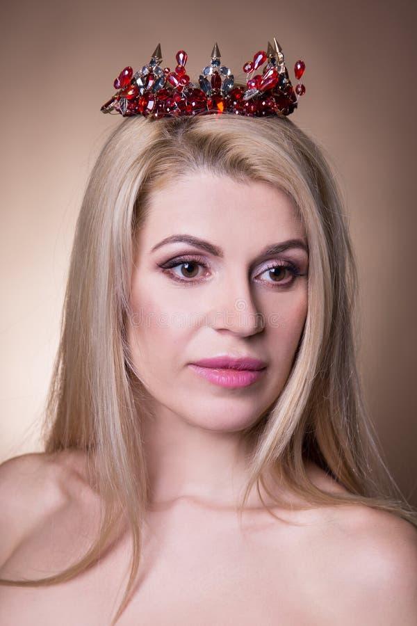 Schließen Sie herauf Porträt des schönen Mädchens mit Krone über Beige stockfoto