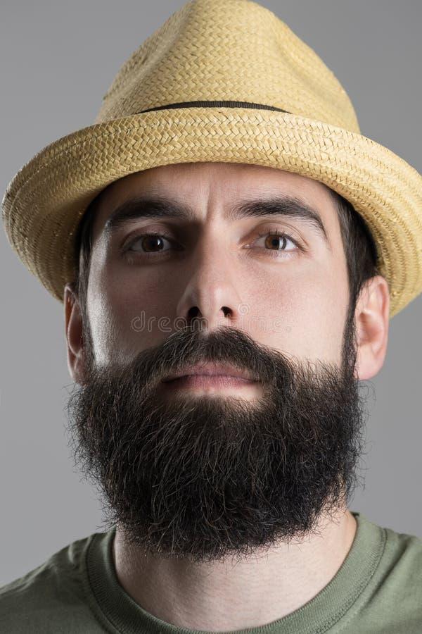 Schließen Sie herauf Porträt des tragenden Strohhutes des überzeugten stolzen Hippies, der Kamera betrachtet stockbild