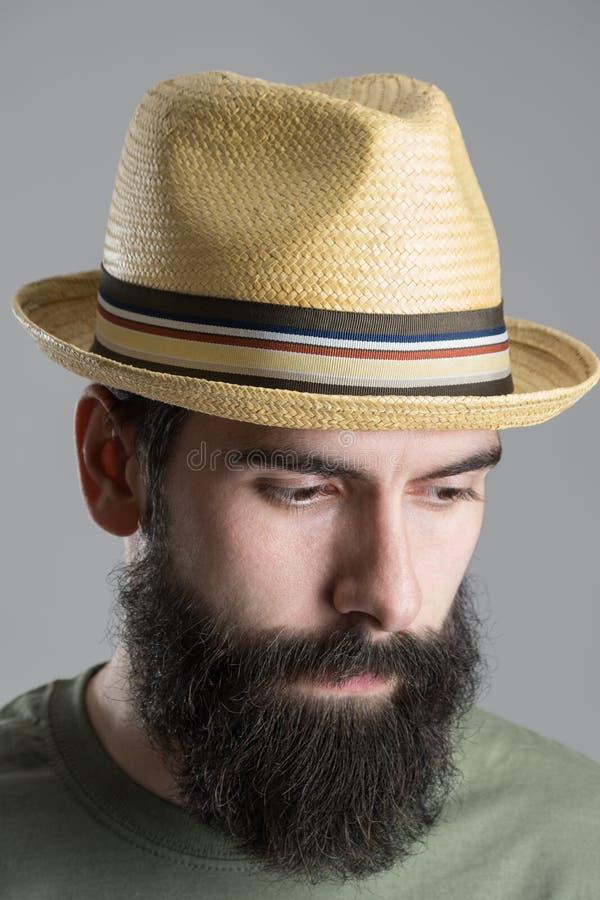 Schließen Sie herauf Porträt des tragenden Strohhutes des bärtigen Mannes, der unten schaut lizenzfreies stockfoto